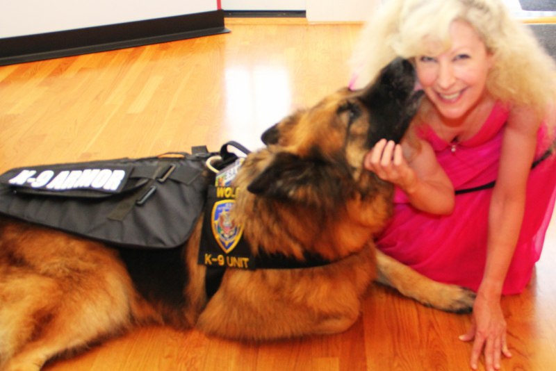 K-9 Armor Co-founder Suzanne Saunders and ESA K-9 Wolfie giving kisses of thanks for donations to protect Monterey Sheriff K9 Heroes. Photo by JelladianArt.com.